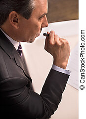 To sign or not to sign. Top view of mature man in formalwear signing a document