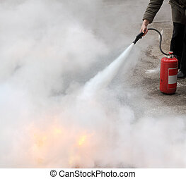 Fire fighting - A woman demonstrating how to use a fire...