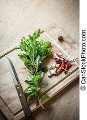 Spices and holy basil herbs on wood chopping block