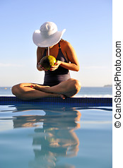 Just relax - Woman relaxing on a swimming pool with a sea...