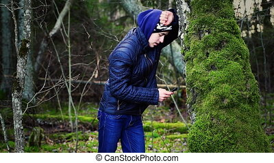 Sorrowful boy with cell phone leaning on a tree