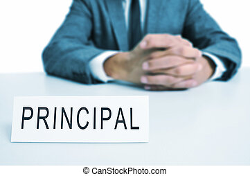 principal - a man wearing a suit sitting in a desk with a...