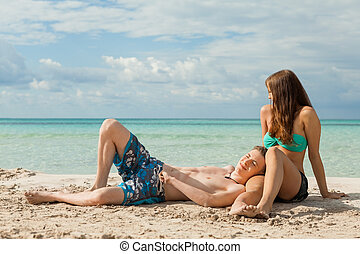 Happy young couple sunbathing - Happy attractive...