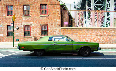 Old vintage car on a street in Brooklyn New York with adobe...
