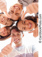 group of smiling teenagers looking down - summer holidays...