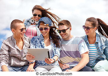 group of smiling teenagers looking at tablet pc - summer...