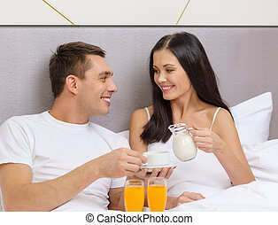 smiling couple having breakfast in bed in hotel - hotel,...