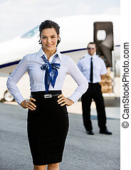 Confident Airhostess With Hands On Hip At Airport Terminal -...
