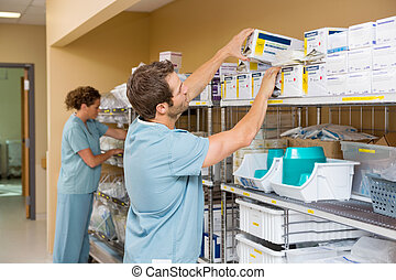 Nurses Arranging Stock In Storage Room - Nurses arranging...