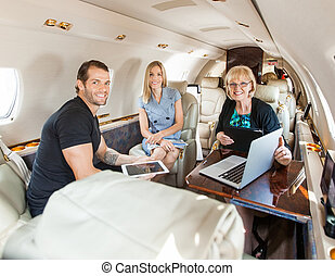Business People Discussing In Private Jet - Portrait of...