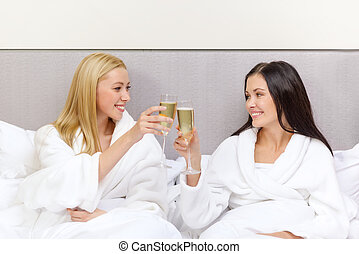 smiling girlfriends with champagne glasses in bed - hotel,...