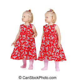 two identical twin girls in red dresses looking - children...