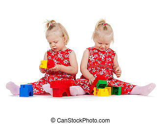 two twin girls in red dresses playing with blocks - children...