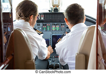 Pilot And Copilot In Private Jet Cockpit - Rear view of...
