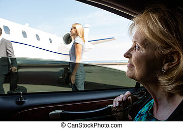 Businesswoman In Car Looking At Private Jet - Thoughtful...