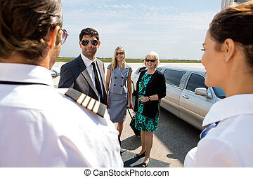 Business Professionals Greeting Pilot And Airhostess At...