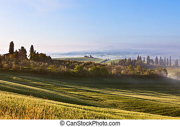 Morning fog view on Tuscan farmhouse