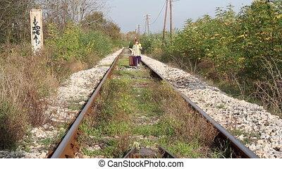 little girl walking on railroad