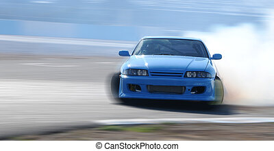 Car drifting on a race track - Blue car drifting on a race...