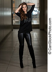 Young Woman Wearing Leather Pants And Long Sleeves