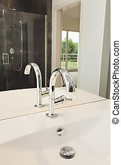 Silver armature in bathroom - tap on a white sink