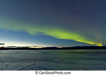 Northern Lights and morning dawn over frozen lake - Intense...