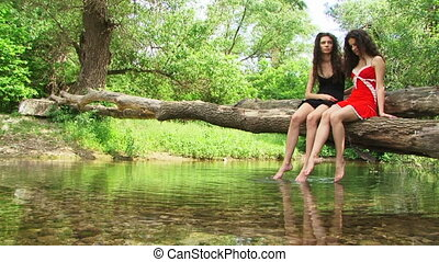 Sisters on a riverside - Sisters sitting on a riverside and...