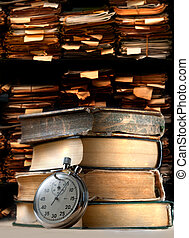 Pile of old books and stopwatch on archive folders...