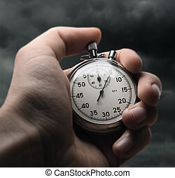 Hand holding stopwatch on stormy sky background