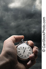 Hand holding stopwatch on stormy sky background