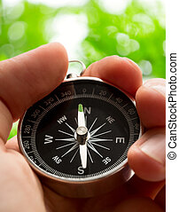 Hand holding compass - Hand holding silver black compass