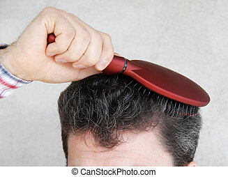 Man brushing hair - Mature man brushing black greyish hair...
