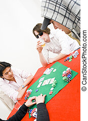 Poker game - Four people sitting around a table with a red...