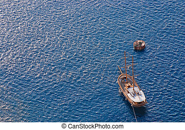 Wooden sailing boat sailing towards the island of Santorini