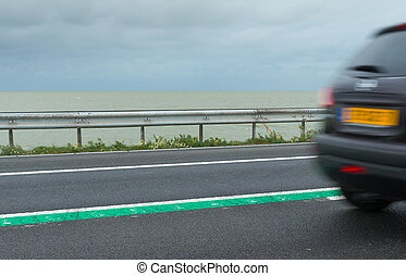 road on dike - car passing on a road on the dike between...