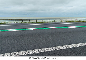 road on dike - road with green line in the middle on the...