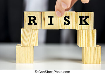 Risk - Building a bridge of wooden cubes with word risk...