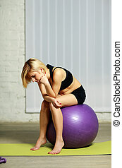 Young pensive fit woman sitting on the fitball