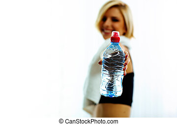Closeup image of female hand holding a bottle with water