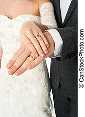 Couple showing their wedding bands - Cropped image of groom...
