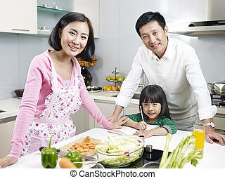 family in kitchen - asian family of three smiling in...