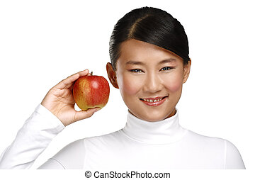 Young pretty asian woman eating an apple on white