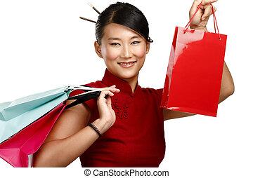 Beautiful asian woman showing multicolor shopping bags
