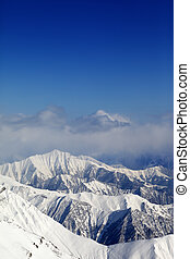 Winter snowy mountains and blue sky with clouds. Caucasus...