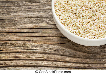 unhulled sesame seeds - a ceramic bowl on grained wood...