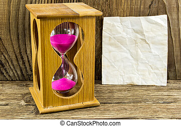 Hourglass with space for text on the wooden background