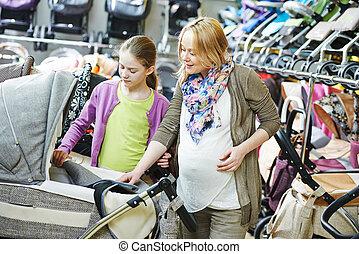 pregnant woman chosing pram - Young pregnant woman choosing...