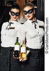 Waitress girl in mask with bottles of wine at restaurant or...