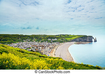 Etretat village, beach and Aval cliff landmark on ocean...