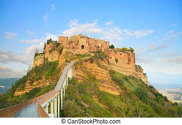 Civita di Bagnoregio landmark, bridge view on sunset. Italy...